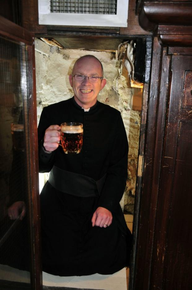 Father Darren Miller sups a pint in the hole