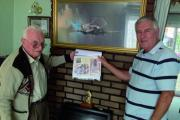 Ronald Turtle and Bob Elliott hold the family history book above the trench art