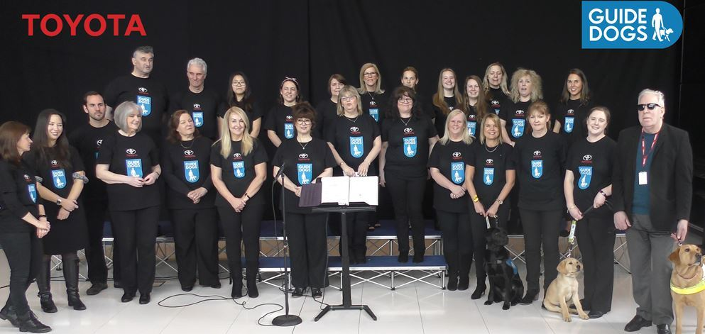 The choir with guests from Guide Dogs, including Miles, Banjo and Iris